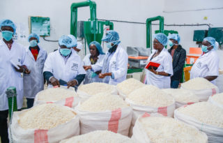 AGRA President Dr. Agnes Kalibata (middle) with an international delegation at Super Seki Investment factory in Iringa Region, Tanzania where they produce fortified maize flour. The company serves over 2,000 smallholder farmers